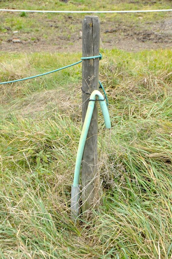 33252 vysokonapěťový kabel pro přívod k ohradě, hadice slouží k mechanické ochraně, u země ještě kovová trubka proti poškození křovinořezem